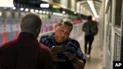 Seorang petugas Dinas Kepabeanan dan Perlindungan Perbatasan memeriksa dokumen migran dari Meksiko yang mengajukan permohonan suaka di AS, di Jembatan Internasional 1 di Nuevo Laredo, Meksiko, 1 November 2019.