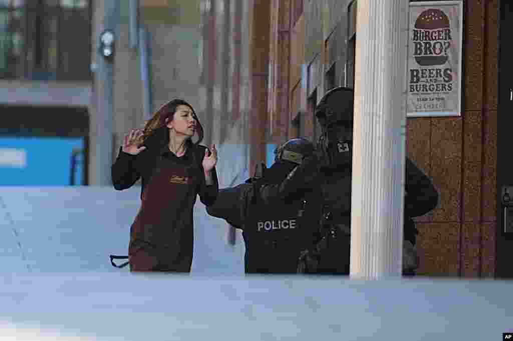 Seorang polisi menangkap seorang sandera yang melarikan diri dari cafe di Martin Place, pusat bisnis di Sydney, Australia, yang dikuasai oleh penyandera (15/12).