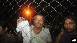 Inmates' relatives stand at the gates of the prison in Comayagua, Honduras, after a fire broke out inside the prison early Wednesday, Feb. 15, 2012.
