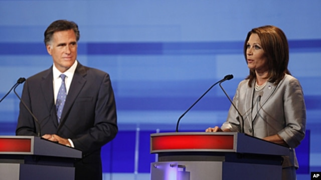 Republican presidential candidates former Massachusetts Gov. Mitt Romney listens to Rep. Michele Bachmann, R-Minn., during the Iowa GOP/Fox News Debate at the CY Stephens Auditorium in Ames, Iowa, Thursday, Aug. 11, 2011