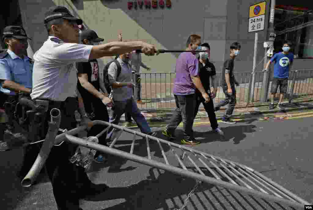 A police officer tries to stop a man who is removing the metal barricades that protesters set up to block off main roads near the heart of the city's financial district, Hong Kong, Oct. 13, 2014.