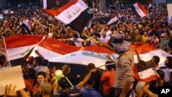 Demonstrators chant in support of Iraqi Prime Minister Haidar al Abadi as they wave national flags during a demonstration at Tahrir Square in Baghdad, Iraq, August 9, 2015.