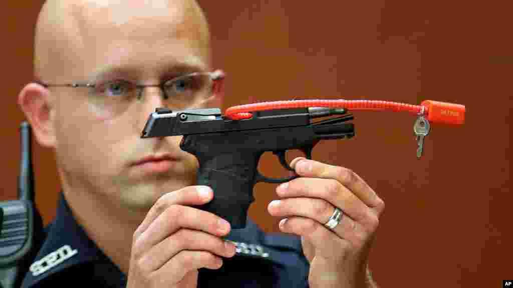 Un policier de Stanford Timothy Smith tient le pistolet qui a été utilisé pour tuer Trayvon Martin, dans le procès George Zimmerman, le 28 juin 2013.