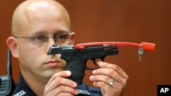 FILE- Sanford police officer Timothy Smith holds up the gun that was used to kill Trayvon Martin, while testifying in the George Zimmerman trial, in Seminole circuit court in Sanford, Florida, June 28, 2013.