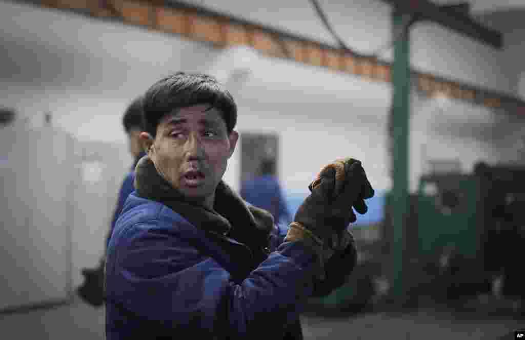 10일 북한 평양326전선공장에서 얼굴에 그을음이 묻은 노동자가 장갑을 벗고 있다. 북한 김정은 국무위원장이 신년사에서 자력자강 중심의 경제발전을 강조한 데 따라, 관영 매체들은 이의 관철을 독려하는 기사를 쏟아내고 당·국가·경제 부문 종사자들의 관련 회의도 열렸다.