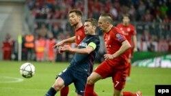 Xabi Alonso de Bayern, à gauche, et son co-équipier Franck Ribéry, à droite, aux prises avec Gabi de Madrid au cours du match retour de demi-finale de football de la Ligue des Champions entre le Bayern Munich et l'Atletico Madrid à Munich, Allemagne, 3 ma