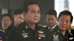 Thailand's Army commander Gen. Prayuth Chan-ocha, left, arrives at the Royal Thai Army Club in Bangkok, Thailand, June 13, 2014.