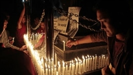 Exiled Tibetans light candles in front of portraits of 21-year-old monk Phuntsog, during a candlelit vigil to honor the monk who set himself on fire in an anti-government protest, in Dharmsala, India, March 17, 2011
