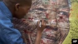 一名南非市民在曼德拉畫像上寫上祝福句語