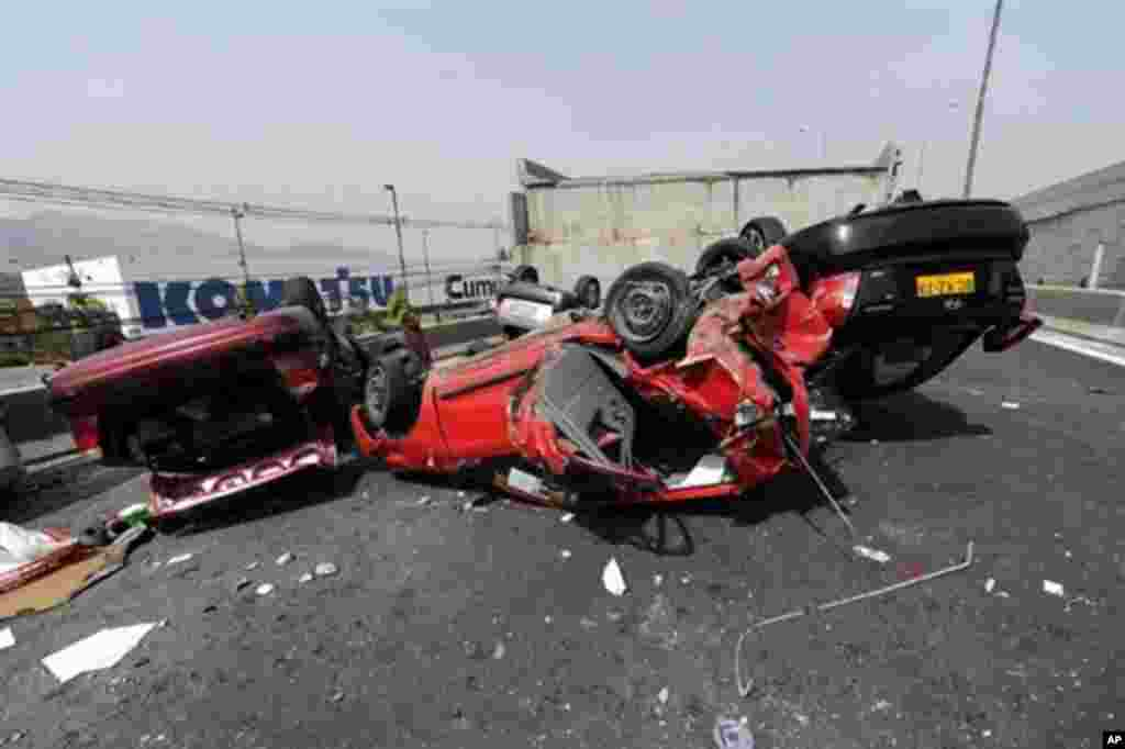 Cars are seen flipped over after a bridge collapsed in Santiago due to a massive 8.8-magnitude earthquake that rocked Chile, 27 Feb 2010