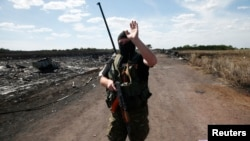 FILE - An armed pro-Russian separatist gestures to reporters at the crash site of Malaysia Airlines Flight MH17, near the village of Grabovo, Donetsk region, Crimea, July 21, 2014.