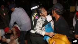 An injured Cambodian is carried by police officers and another visitor after a stampede in Phnom Penh, Cambodia, Monday, Nov. 22, 2010. Thousands of Cambodians celebrating a water festival by the river in the Cambodian capital stampeded Monday night,