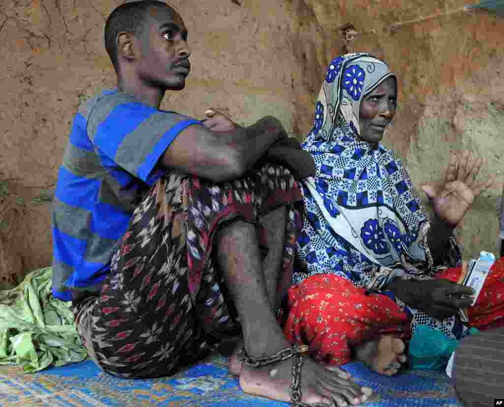 Siyad Abdi Ali, 24, with his mother at the refugee camp. Ali developed an unidentified mental illness after he was allegedly tortured by Ethiopian troops before coming to the camps. His family keeps him restrained to prevent him from harming himself. (VOA