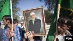 Para pendukung Burhanuddin Rabbani membawa foto almarhum di luar rumahnya, sehari setelah terjadinya pembunuhan (21/9). Rabbani dibunuh oleh pembom bunuh diri yang membawa pesan perdamaian palsu.
