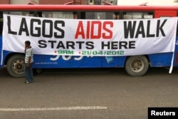 FILE - A man walks past a banner tied on a bus before the start of a charity walk on HIV/AIDS at the Ebute Mata district in Nigeria's commercial capital Lagos, April 21, 2012.