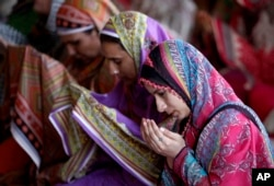 FILE - Pakistani women offer Friday prayers at historical Badshahi mosque during the holy fasting month of Ramadan, in Lahore, Pakistan, June 24, 2016.