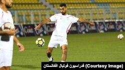 یکی بازیکنان تیم ملی فلسطین حین ضربه زدن به توپ
