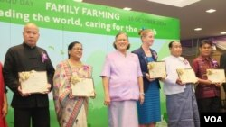 """Model"" family farmers from China, India, New Zealand, Myanmar and Thailand hold their FAO citations as they pose with Princess Maha Chakri Sirindhorn."