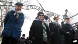 """Ngững người sống sót và khách đi ngang qua cổng trại tập trung """"Arbeit Macht Frei"""" dưới thời Đức Quốc Xã nhân lễ kỷ niệm Ngày Holocaust Quốc tế tại Oswiecim, Ba Lan, ngảy 27/1/2018."""