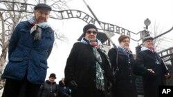 Учасники вшанування Міжнародного дня пам'яті Голокосту біля воріт до колишнього німецького нацистського табору смерті Аушвіц в Освенцимі у Польщі 27 січня 2018 р.