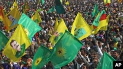 Thousands of PKK supporters demonstrate with flags and posters of jailed Kurdish rebel leader Abdullah Ocalan, in southeastern city of Diyarbakir, Turkey, March 21, 2013.
