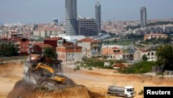 An excavator demolishes a lone house at the construction site of an urban transformation project in Fikirtepe, an Istanbul neighborhood in the Asian part of the city, Turkey, Aug. 14, 2014.