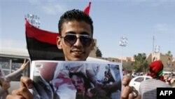 Một người cầm bức ảnh thi hài của ông Gadhafi