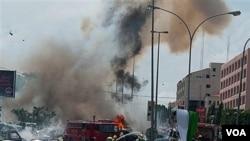 Regu pemadam kebakaran berusaha memadamkan kobaran api akibat serangan bom di Abuja, Nigeria pekan lalu.