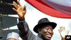 Shugaba Goodluck Jonathan na Nigeria ne yake daga wa taron jama'a hannu kafin kaddamarda gangamin kyamfen dinsa na neman zabe a Abuja, Nigeria.