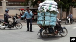 A Cambodian man, right, drive his motorbike overloaded with vegetable sacks as he passes a traffic police officer, center, in Phnom Penh, Cambodia, Tuesday, Aug. 25, 2015. (AP Photo/Heng Sinith)