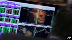 Specialist Frank Masiello is reflected in his screen on the floor of the New York Stock Exchange, Aug. 24, 2015.