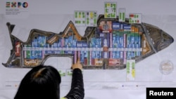 A visitor looks at an Expo map inside the Expo 2015 work site near Milan, Italy, April 27, 2015.