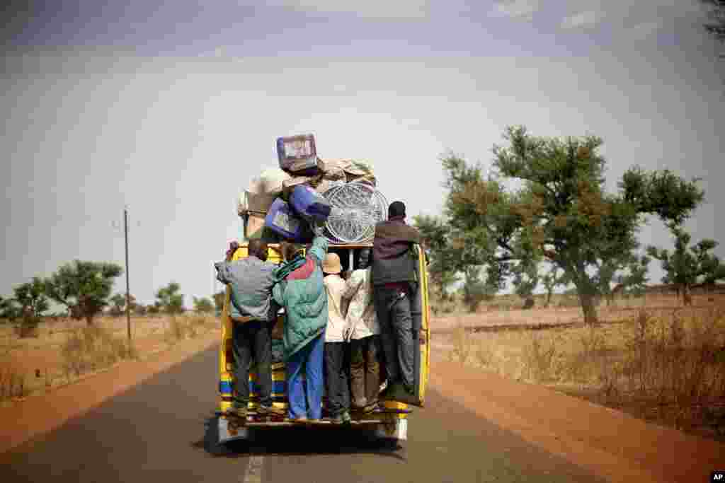 Malians hang on the back of a packed minibus as they drive to Marakala, central Mali, 240 kilometers from Bamako, January 22, 2013.