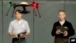 FILE - Students at the University of North Dakota in Grand Forks remotely pilot a drone during a demonstration, June 24, 2014. The Federal Aviation Administration now requires drone registration.
