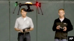 FILE - Students at John D. Odegard School of Aerospace Sciences at the University of North Dakota in Grand Forks, North Dakota, remotely pilot a drone during a demonstration, June 24, 2014.