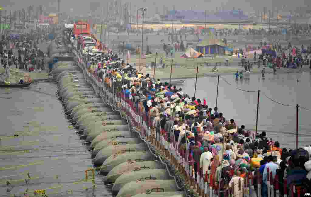 인도 알라하바드에서 힌두교 마그멜라 축제에 참가한 순례자들이 물에 몸을 담그는 성스러운 의식을 행하기 위해 부교를 건너고 있다.