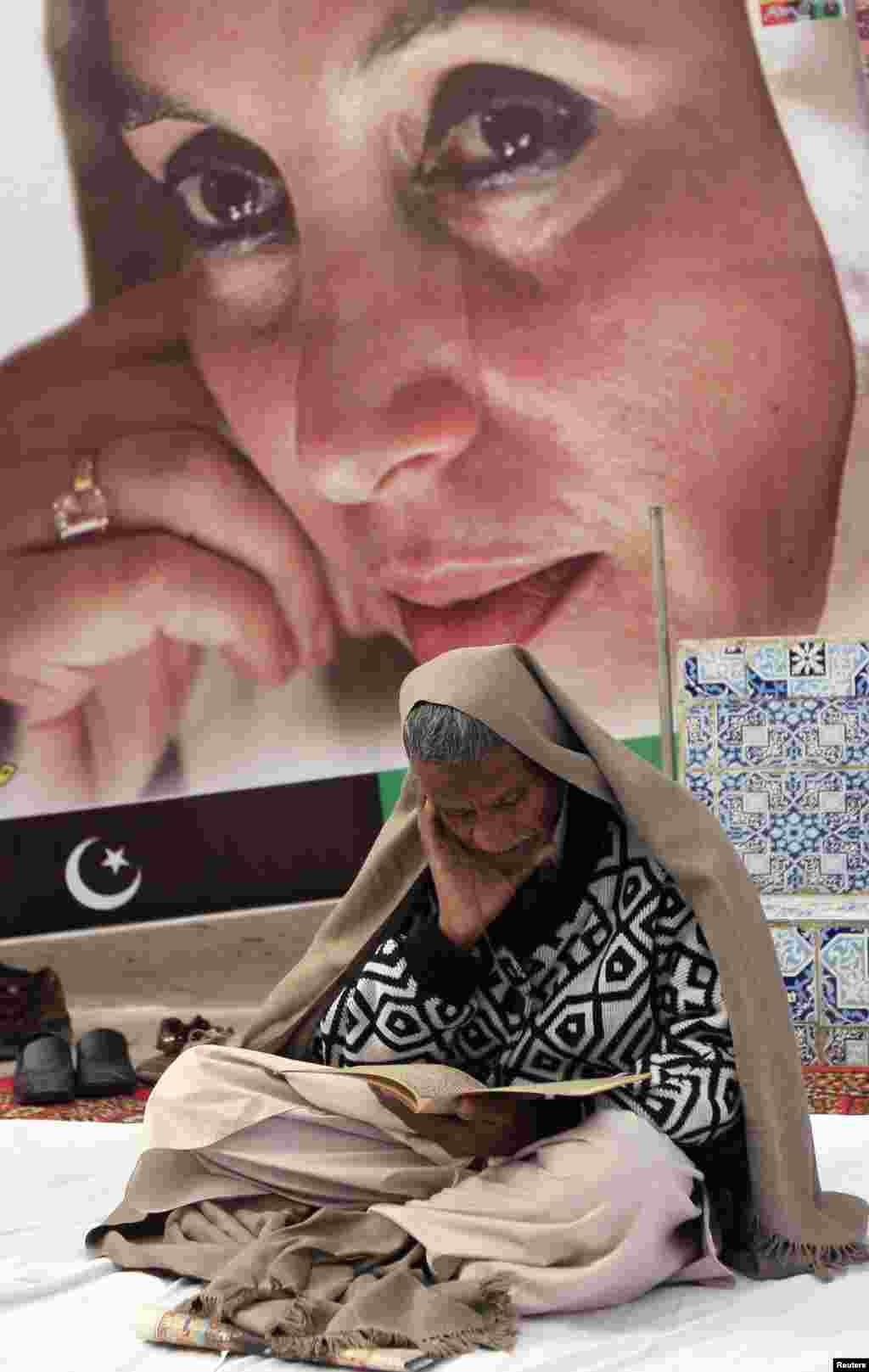 ایک کارکن بے نظیر بھٹو کی روح کے ایصال ثواب کے لیے قرآن خوانی کر رہا ہے