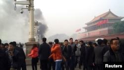 Người đi bộ dọc Đại lộ Trường An trong lúc khói bốc lên từ vụ cháy xe tại Quảng trường Thiên An Môn, gần cổng chính để vào Tử Cấm Thành tại Bắc Kinh, ngày 28/10/2013