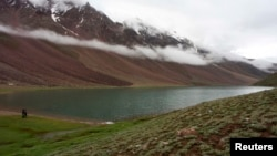 Tourists look at clouds hanging over Chandra Taal Lake in the Lahoul & Spiti district, in the northern Indian state of Himachal Pradesh, July 15, 2009.
