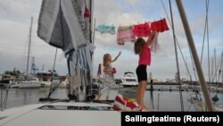 Katalin Bosze and Boroka Bosze hang their clothes to dry on the sailing boat 'Teatime' in Las Palmas, Spain. Picture taken on October 5, 2020. (Sailingteatime via Reuters)