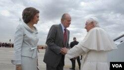 Paus Benediktus XVI (kanan) disambut oleh Raja Spanyol Juan Carlos dan Ratu Sofia saat tiba di bandara Madrid (18/8).
