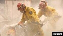Petugas mencari korban di antara puing-puing rumah yang terbakar di Paradise, California (13/11).