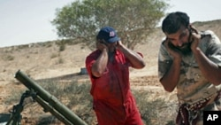 Revolutionary fighters firing a mortar at Gadhafi loyalist positions in Sirte, Libya, Monday, Sept. 19, 2011