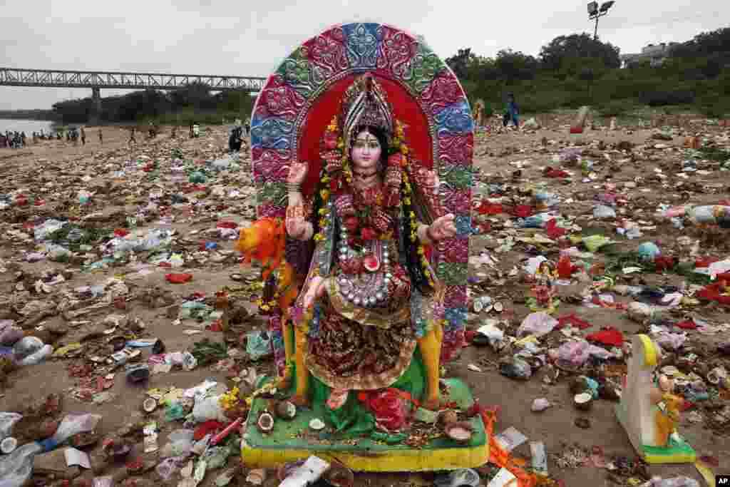 Patung Dewi Hindu Dashama berdiri di antara benda-benda sesaji dan persembahan di tepi sungai Sabarmati pada festival Dashama di Ahmadabad, India.