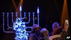 People take pictures in front of a Menorah during the Jewish festival of Hannukah, in Istanbul, Dec, 24, 2016. Hanukkah, known as the Jewish Festival of Lights, is celebrated for eight days.