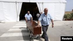 Pekerja rumah sakit membawa peti jenazah salah seorang migran yang tewas di Laut Tengah untuk dimakamkan di Tal-Qroqq, di dekat Valletta, ibukota Malta.