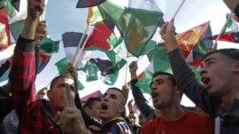 People wave Palestinians flags during celebrations for their successful bid to win U.N. statehood recognition in the West Bank city of Ramallah, Dec. 2, 2012.