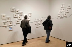 """In this March 15, 2018, photo, two men look at the conceptual project """"The People's View"""" by Dutch artist Rein Jelle Terpstra that is part of the exhibit, """"The Train: RFK's Last Journey,"""" at the San Francisco Museum of Modern Art in San Francisco. The photographs, taken by bystanders, are arranged on the wall by where they were taken on the route from New York City to Washington."""