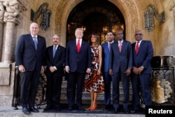 U.S. President Donald Trump and first lady Melania Trump pose with Saint Lucia Prime Minister Allen Chastanet (L), Dominican Republic President Danilo Medina (2ndL), Jamaica's Prime Minister Andrew Holness (3rdR), Haiti's President Jovenel Moise (2ndR), Bahamas Prime Minister Hubert Minnis (R) and other leaders prior to a working visit at Mar-a-Lago in Palm Beach, Florida, March 22, 2019.