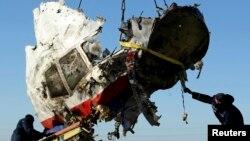 Công nhân địa phương thu hồi một mảnh của chiếc phi cơ MH17 của hãng hàng không Malaysia Ailines tại địa điểm phi cơ rơi gần làng Hrabove, trong vùng Donetsk, miền đông Ukraine